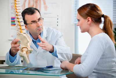 Doctor shows to patient the problem areas on the model of the spine